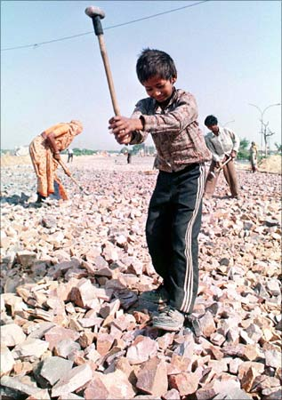 Sunny, a 6-year-old labourer who has never been to a school, and his family members break stones at a road construction site in New Delhi.