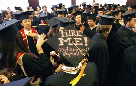 A graduating student displays a 'Hire me' sign written on his mortar board.
