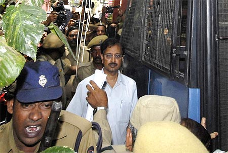 Ramalinga Raju, founder and former chairman of fraud-hit Satyam Computers, is escorted from a court in Hyderabad on April 9, 2009.