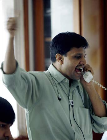 A happy investor reacts as he speaks on the phone.