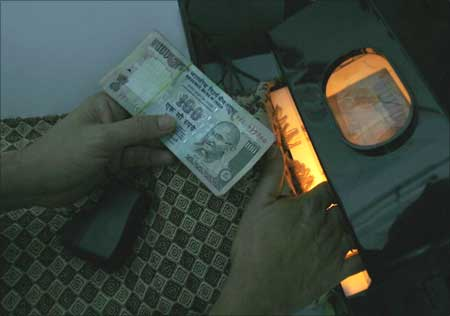 A man uses an electronic machine to check a hundred rupee note.