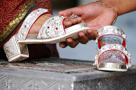 A customer tries sandals made from silver, with wooden soles, in the northern Indian city of Lucknow. Nearly 225-300 grams of silver are used on each pair.