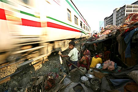 A family takes shelter in their home next to a railway track as a train zips by.