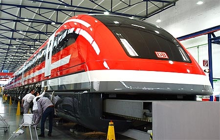 Workers polish a prototype of the new maglev Transrapid high-speed train in German city of Kassel.