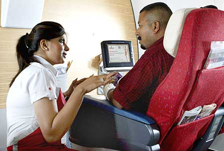 A stewardesses explains the features of the in-flight entertainment system to a Kingfisher passenger