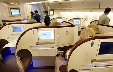 People look at the newly introduced premier class cabin in a Jet Airways Boeing 777-300 ER.