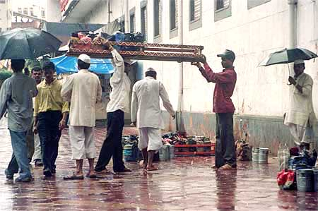 A dabbawallah helps his colleague lift a crate full of tiffin boxes