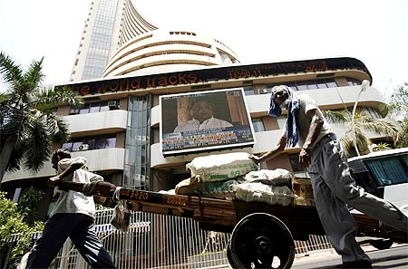 Workers pull a hand-cart in front of the Bombay Stock Exchange building in Mumbai.