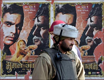 An Indian policeman stands in front of movie posters in Srinagar.