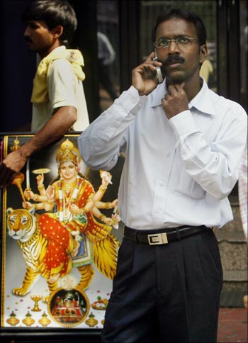 A man speaks on a his mobile as he looks at a large screen displaying India's benchmark share index.