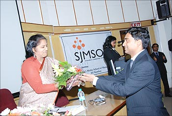 A student presents a bouquet to Karuna Jain.