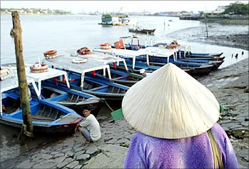 A Vietnamese woman prepares to board a small ferry used to shuttle commuters across the Saigon River near the port in Ho Chi Minh City.
