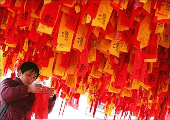 A Chinese woman hangs an ornament on a tree outside a temple in Shanghai.