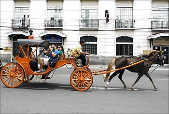 Tourists ride on a 'Kalesa', a horse drawn carriage in Manila.