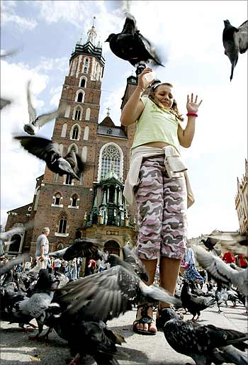 A girl reacts as she feeds pigeons near the Mariacki Church in Old Square in Krakow, Poland.