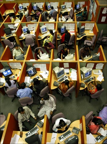 Indian employees seated in their cubicles at a call centre.