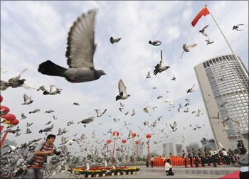 Pigeons are released during a flag raising ceremony to mark the 60th anniversary of the founding of the People's Republic of China.