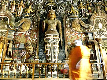 A buddhist monk walks into a temple in Colombo.