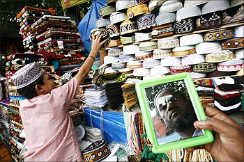 A customer tries on a prayer cap at the new market area in Dhaka.