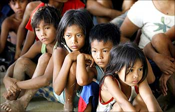 Children from flood-hit town Rosales, Pangasinan wait for the distribution of relief supplies by U.S. Marines.
