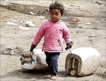A girl drags containers to collect water at Dar El Salam, Cairo.