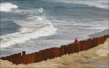 A woman walks next to a wall construction site at south Coogee beach in Sydney.