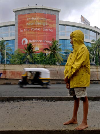 A boy looks at an auto rickshaw passing by the Reliance Energy building in Mumbai.