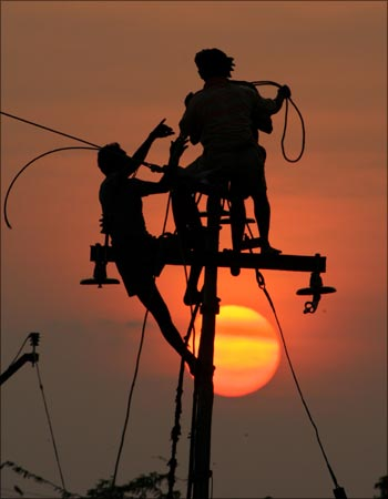 Workers install electric cables on a lamp post in Nagapattinam near Chennai.