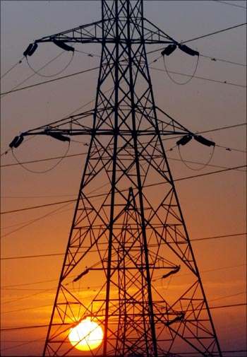 The sun rises behind electric pylons in Ahmedabad.