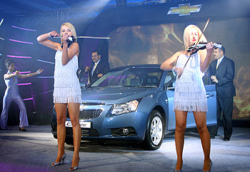Models pose with violin at Chevrolet Cruze launch in Mumbai.