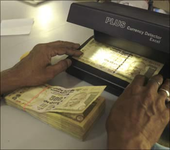 A cashier checks Indian currency notes inside a bank in Agartala.
