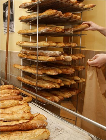 A worker displays baguettes (French stick), bread made with organic flour, at a bakery in Paris.