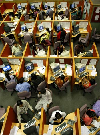 Employees seated in their cubicles at a call centre.