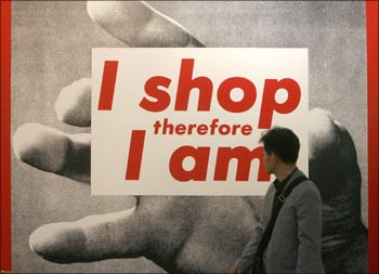 A man looks at a sign 'I shop, therefore I am', highlighting American consumerism.