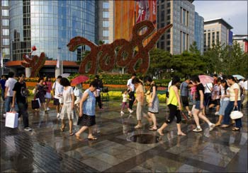 People walk past a shopping centre near Tiananmen Square in Beijing.