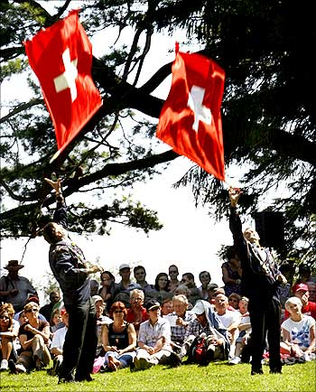Traditionally dressed men take part in flag tossing during Switzerland's national holiday celebrations.