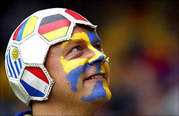 A Sweden fan wearing a hat made from a football waits before Sweden's soccer match against Spain.