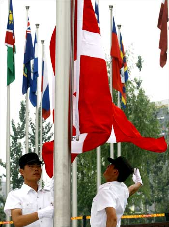 Chinese officials raise the flag of Denmark during the official flag raising ceremony in the Olympic Village ahead of the Beijing 2008 Olympic Games.