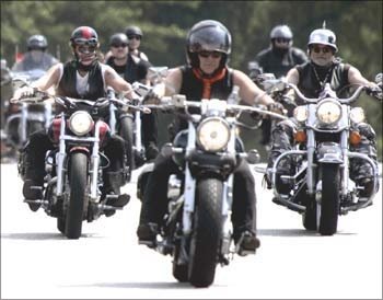Bikers ride their Harley-Davidsons.
