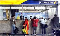 Passengers speak with employees at the Jet Airways ticketing counter at the Mumbai airport.