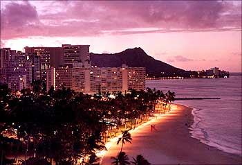 A view of downtown Honlulu shows the famous Waikiki Beach at sunrise with Diamond Head rising in the background.