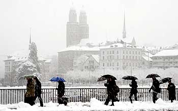 People cross the Quaibruecke bridge in front of the Grossmuenster church during snowfall in Zurich.