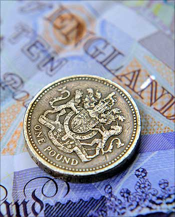A one pound coin and sterling notes are seen in central London.
