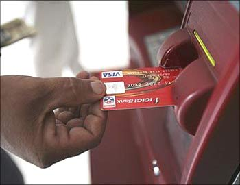 A man using an ATM in Mumbai.
