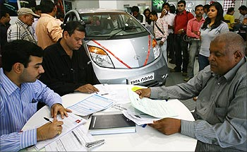Customers fill forms to book the Tata Nano at a showroom in New Delhi.