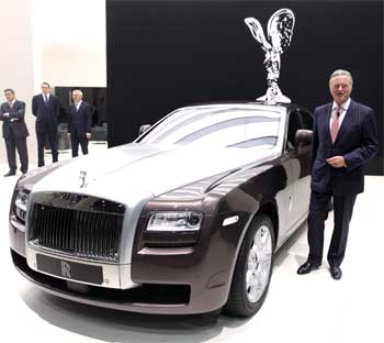 Rolls Royce CEO Tom Purves stands next to a Rolls Royce Ghost.