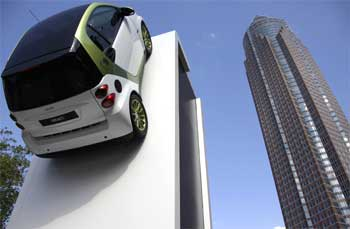 An electric car is displayed on a wall next to the fair tower.