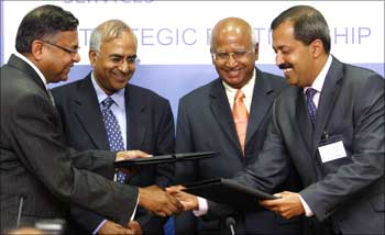 N. Chandrasekaran (L), exchanges documents with Sanjar Nayar (R), former CEO of Citi Bank.