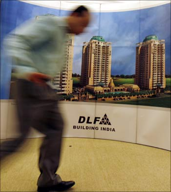 A man walks past a banner of Indian property developer DLF Ltd.