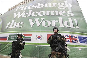 Security personnel stand guard in front of a welcome banner on the Hilton Hotel in downtown Pittsburgh, Pennsylvania.